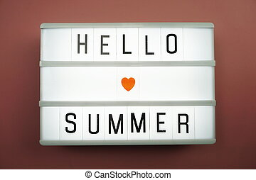 Hello Summer word in light box on white brick wall and wooden background