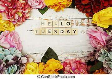 Hello Tuesday alphabet letter with colorful flowers border frame on wooden background