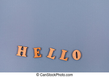 Hello word written in wooden alphabet letters on a gray background. Text on the table for design or concept.