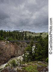 Hellroaring Creek Cuts Through Canyon Under Suspension Bridge