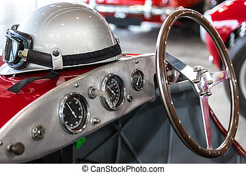 Helmet and glasses on a luxury convertible sports car.