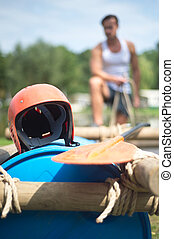 Helmet and oar on inflatable raft - A protective helmet and...