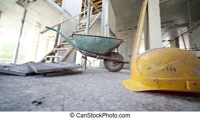 Helmet lies on floor in front of wheelbarrow in unfinished premises