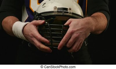 Helmet of American Football Player in his hands. Safety.
