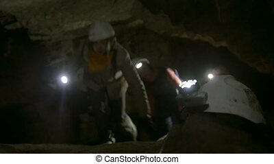 Helmet with flashlight in front of speleologists explores...