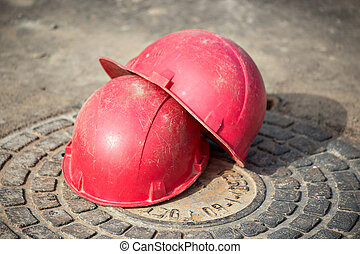 Helmets - Two red helmets on the manhole