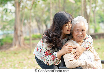 Help and care Asian senior or elderly old lady woman patient sitting on wheelchair at nursing hospital ward : healthy strong medical concept