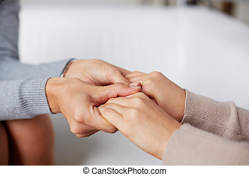 Help - Close-up of psychiatrist hands holding those of her...