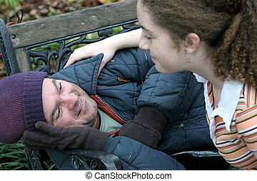 A homeless man being helped by a teen volunteer. (focus on homeless man's eyes)