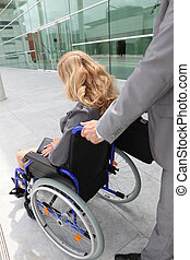 help handicapped woman on wheelchair