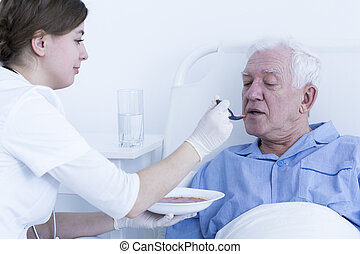 Help in everyday actions - Young nurse feeding the senior...