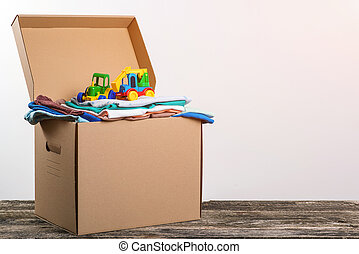 Help poor. Box full of clothing and toys for poor families. Sharity social activity. Donation concept.