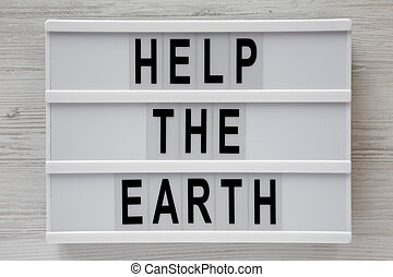 'Help the Earth' words on lightbox over white wooden background, top view. Flat lay, overhead, from above.