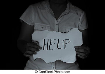 HELP, Woman with help sign. girl holding a paper with the inscription. girl in casual clothes holding sheet of paper. Girl holding sheet of paper with word HELP on black wall background