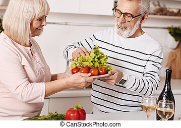Helpful aged couple preparing family dinner together in the kitchen