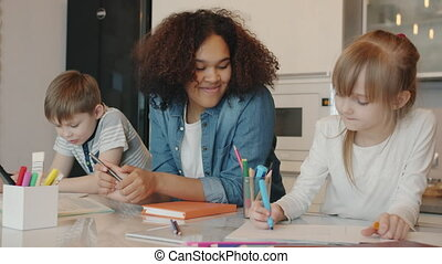 Helpful Afro-American babysitter is talking to kids doing homework writing and drawing at table. Home schooling and happy childhood concept.