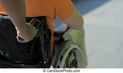 Helpful caregiver pushing a wheelchaired man