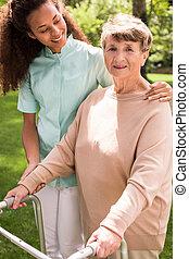 Helpful caregiver with senior - Image of helpful caregiver...