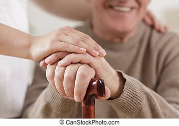 Helpful carer and happy old man - Close up of helpful carer...