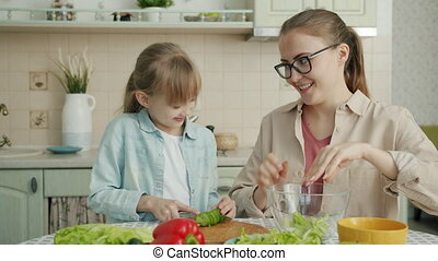 Helpful daughter is making vegetable salad chopping cucumber while young loving mother is touching her hair expressing love at home in kitchen.