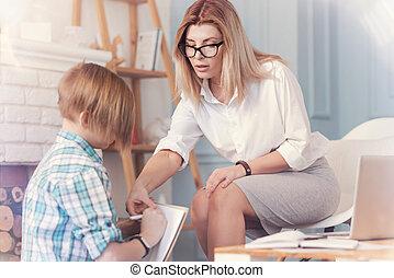 Helpful female psychologist working with a school boy