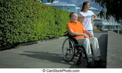 Helpful female volunteer resting with a wheelchaired man