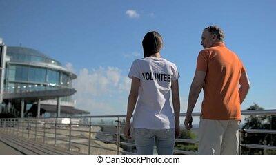 Helpful female volunteer walking with a senior man