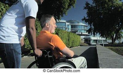 Helpful hindu volunteer standing with a wheelchaired man in the park