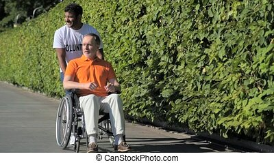 Helpful hindu volunteer walking with a wheelchaired man