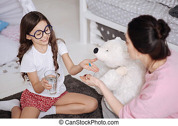 Helpful little girl and mother taking care of toy at home