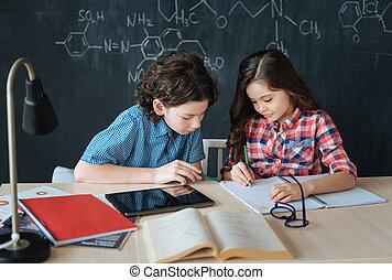 Helpful little pupils enjoying lesson at school - Helping...