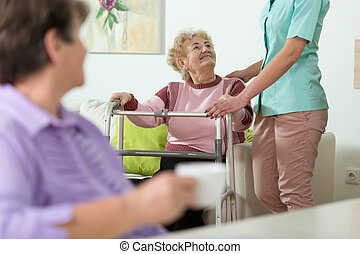 Helpful nurse - Young helpful nurse and older woman with...