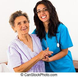 Happy joyful nurses caring for kind elderly patients helping their days in nursing home.