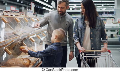 Helpful son is helping his parents to buy bread , father is opening container and boy is taking loaf and smelling it then putting in trolley. Shopping together concept.