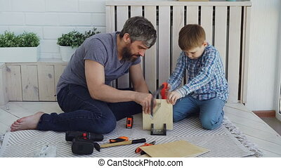 Helpful son is sawing sheet of wood with hand saw while his...