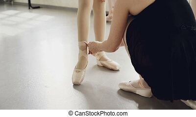 Helpful teacher is putting pointe-shoes on little student's...