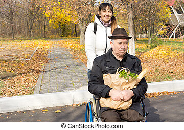 Helpful woman pushing a senior man in a wheelchair as they...