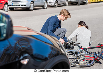 Helpful young man giving first aid to an injured woman after bicke accident