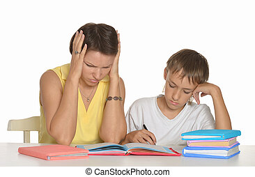 Helping doing homework - Mother helping her teen son doing...