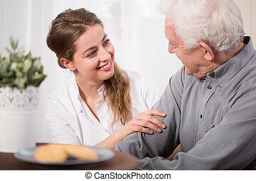Helping elderly people - Young volunteer visiting elder man...