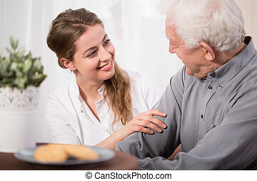Helping elderly people - Young volunteer visiting elder man...