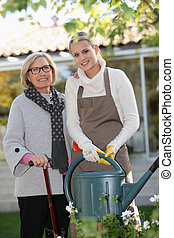 Helping elderly woman in the garden