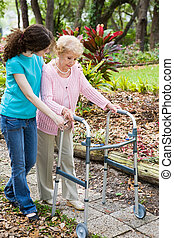 Teen girl helping her grandmother cope with a walker.