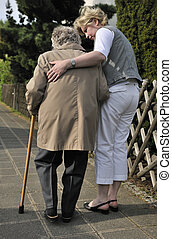 Helping hand - Senior woman walking with the help of a ...