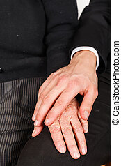 Helping hand - Young reassuring hand on wrinkled elderly...