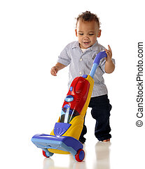 Helping Mommy - A mixed race toddler vacuuming with his toy ...
