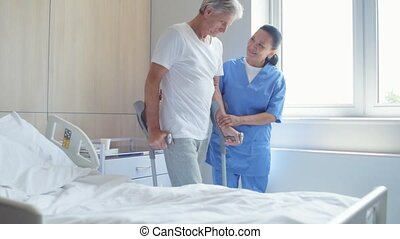 Helping nurse helping a senior man to walk on crutches -...