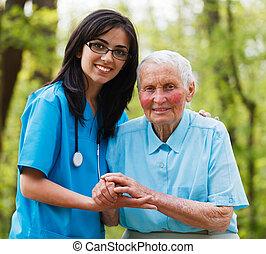 Helping Nurse - Kind nurse together with elderly woman in...