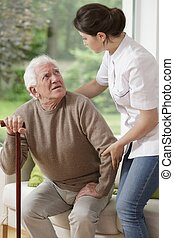 Helping old man - Woman helping old man to stand up
