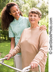 Helping old woman - Nurse is helping old woman with walking